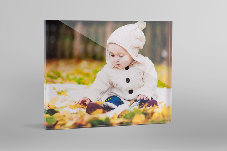 Personalised desk gift of a glass photo block of a baby in the autumn leaves